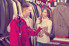 Couple deciding on warm suit in men's cloths store Stock Photography