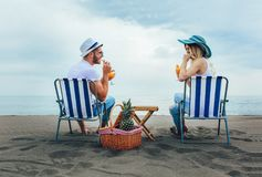 Couple on a deck chair relaxing on the beach. stock image