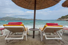 Couple of deck chairs on the beach with thatched umbrella Royalty Free Stock Photos