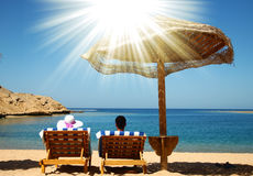 Couple on deckchairs by the sea Stock Photography