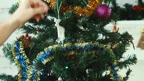 A couple decorate a Christmas tree. A couple of young people decorate a Christmas tree stock footage