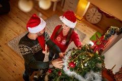 Couple decorate Christmas tree Royalty Free Stock Photos