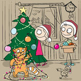Couple decorates Christmas tree. Red cat tangled in garland Royalty Free Stock Photos
