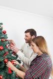 Couple decorating the christmas tree stock photo