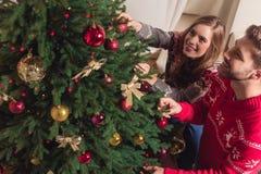 Couple decorating christmas tree. High angle view of happy young couple decorating christmas tree together Stock Image
