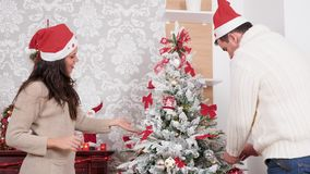 Couple decorating a Christmas tree in the living room. Caucasian couple decorating a Christmas tree in the living room stock video