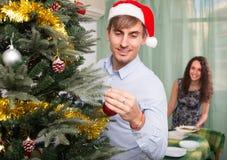 Couple decorating Christmas tree Stock Photography