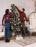 Couple decorating the family Christmas tree Stock Images