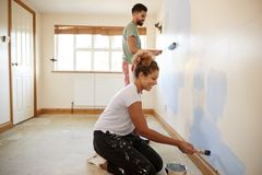 Couple Decorating Room In New Home Painting Wall Together stock photo