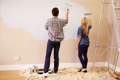 Couple Decorating Room Using Paint Rollers On Wall Stock Photos