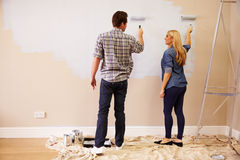 Couple Decorating Room Using Paint Rollers On Wall Royalty Free Stock Photo