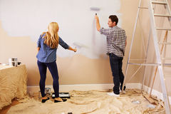 Couple Decorating Room Using Paint Rollers On Wall Stock Image