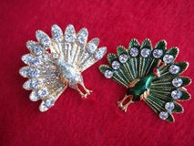 Couple of decorations peacock shape. Couple of white and green decorations peacock shape on red background Stock Image