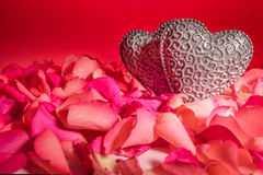 Couple of decorative carved hearts in red rose petals. On red background Stock Photos