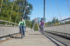 Couple on DeFazio Bike Bridge. A happy couple ride their bicycles on a sunny day across the DeFazio Bike Bridge in Eugene Oregon stock image