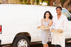 Couple Delivering Pizza Standing In Front Of Van Royalty Free Stock Images