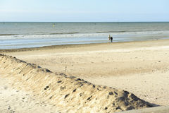Couple on deserted beach looking at the sea on a sunny day Royalty Free Stock Photo