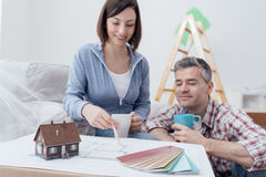 Couple designing their deam house. Happy couple designing their new house, they are checking the house project together and doing home renovations Royalty Free Stock Photo