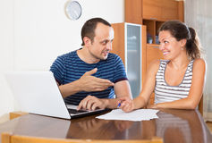 Couple at desk with papers and laptop Stock Photos