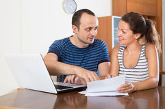 Couple at desk with papers and laptop Stock Images