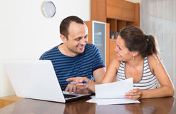 Couple at desk with papers and laptop stock photography