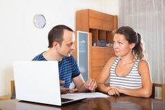 Couple at desk with papers and laptop Royalty Free Stock Photography