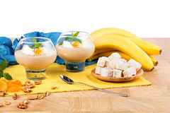 A couple of dessert glasses isolated on a white background. Smoothies next to bananas, Turkish delight, and walnuts. Royalty Free Stock Photos