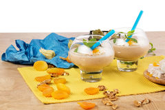 A couple of dessert glasses isolated on a white background. Smoothies next to dried apricots, Turkish delight, and Stock Image