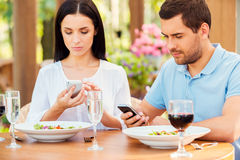 Couple from digital age. Young couple typing something on their smart phones while relaxing in outdoors restaurant together royalty free stock images