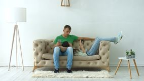 Couple with digital devices relaxing on the couch stock video footage