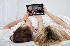 Couple with digital tablet in bedroom Stock Images