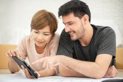 Couple with digital tablet and blueprints planning their new moving house. royalty free stock photography