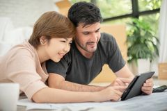 Couple with digital tablet and blueprints planning their new moving house. Happy young couple with digital tablet and blueprints planning their new moving house stock photography