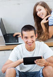 Couple with digital tablet and laptop Stock Image