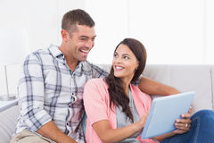 Couple with digital tablet sitting on sofa Royalty Free Stock Photography