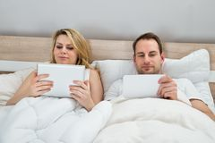 Couple with digital tablets Stock Images