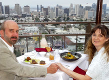 A Couple Dine Overlooking Downtown San Diego. A Middle Aged Couple Dine Overlooking the Downtown San Diego Cityscape stock photo