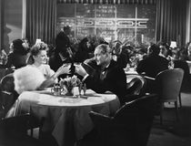 Couple dining in crowded restaurant. (All persons depicted are no longer living and no estate exists. Supplier grants that there will be no model release issues stock image