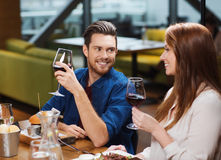 Couple dining and drinking wine at restaurant. Leisure, eating, food and drinks, people and holidays concept - smiling couple having dinner and drinking red wine Royalty Free Stock Images