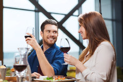 Couple dining and drinking wine at restaurant. Leisure, eating, food and drinks, people and holidays concept - smiling couple having dinner and drinking red wine Stock Photo