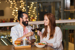 Couple dining and drinking wine at restaurant. Leisure, eating, food and drinks, people and holidays concept - smiling couple having dinner and drinking red wine Stock Images