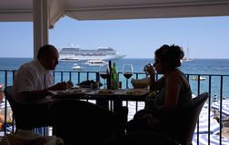 Couple dining in foreground with cruise ship in background at Amalfi, a town in the province of Salerno, in the region of Campania Stock Image