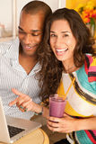 Couple Dining Out Using a Laptop. Two people at a cafe drinking frozen beverages and using a laptop. Vertical shot Royalty Free Stock Photos
