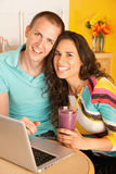 Couple Dining Out Using a Laptop. Two people at a cafe drinking frozen beverages and using a laptop. Vertical shot Stock Images