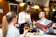 Couple dining in a restaurant. Beautiful couple dining in a restaurant while happy waitress is taking their order Royalty Free Stock Photo