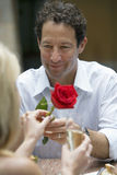 Couple dining in restaurant, focus on man giving woman single red rose, smiling Royalty Free Stock Photos