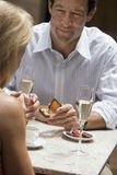 Couple dining in restaurant, focus on man holding engagement ring, proposing to woman, smiling Royalty Free Stock Image