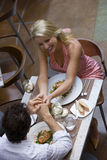Couple dining in restaurant, holding hands, elevated view Royalty Free Stock Photo