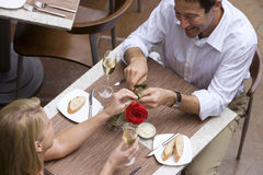 Couple dining in restaurant, man giving woman red rose, elevated view Stock Photography