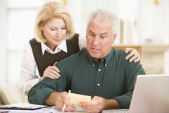 Couple in dining room with laptop and paperwork royalty free stock photo